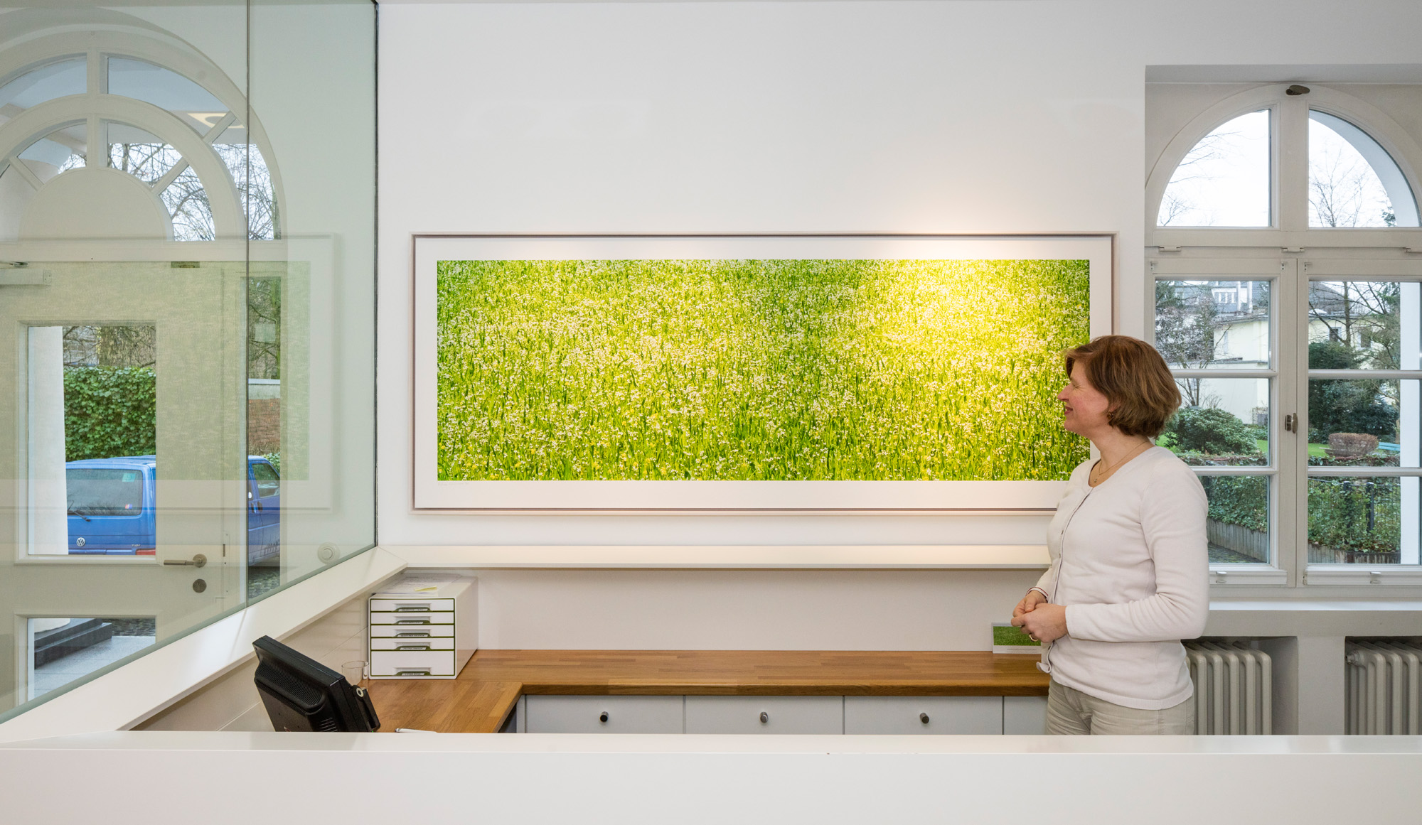 "Villa Vita Köln, Dr. Katharina Sprenger vor dem Bild ""Mallorca Weiße Blüten"""